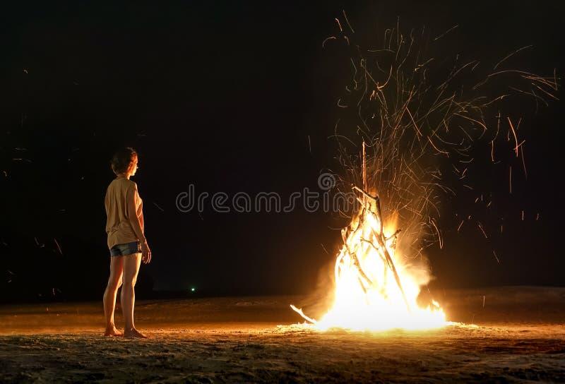 少妇旅客海滩篝火感觉热与火花的 免版税库存图片