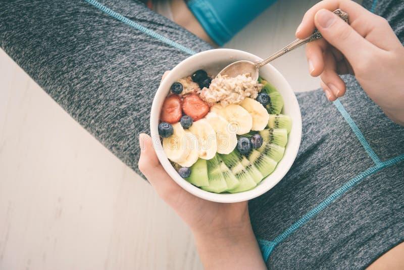 少妇是休息和吃一个健康燕麦粥在锻炼以后 库存图片