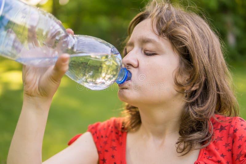 少妇是从瓶的饮用水晴朗的热的天 免版税库存照片