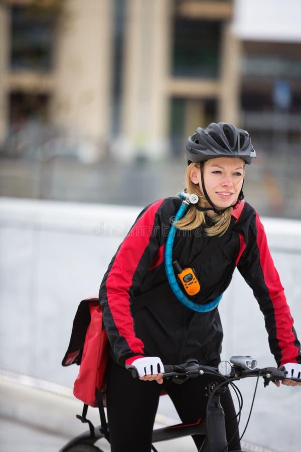 少妇有传讯者交付的骑马自行车 免版税图库摄影