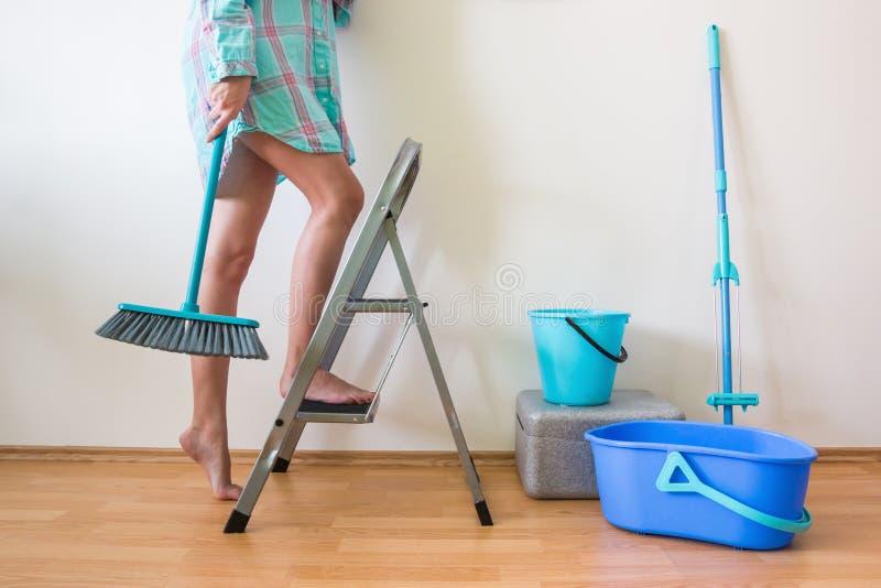 少妇有梯子和刷子的清洁家 免版税图库摄影