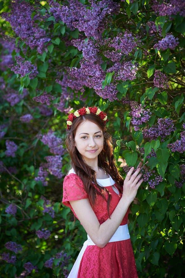 少妇有花圈的和有淡紫色花的春天 免版税库存图片