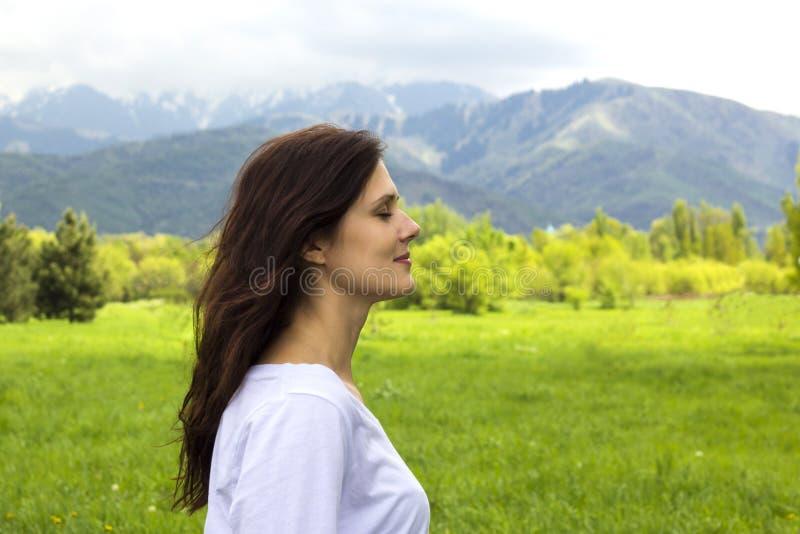 少妇档案有眼睛的关闭了在山的呼吸的新鲜空气 免版税库存照片
