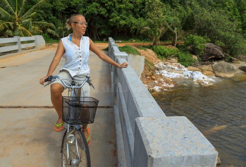 少妇横跨河桥梁的骑马自行车在热带公园旁边 免版税库存照片