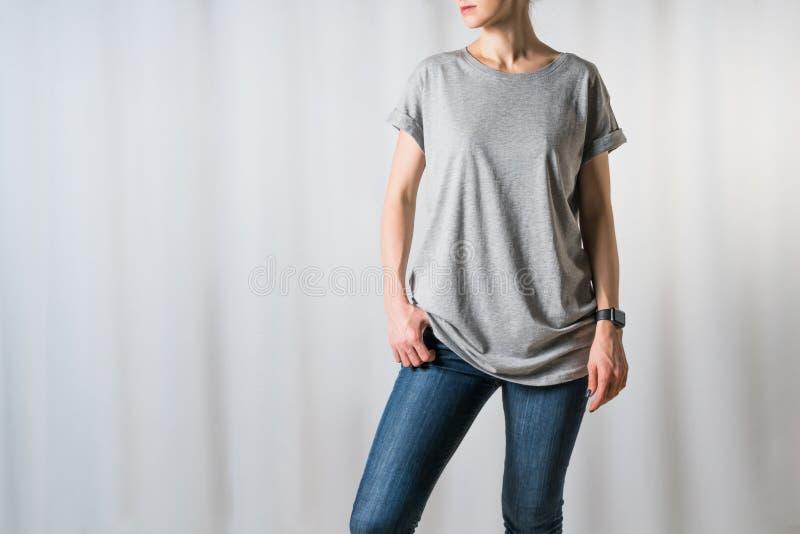 少妇正面图,穿戴在一件灰色T恤杉和蓝色牛仔裤,站立在浅灰色的背景 免版税库存图片