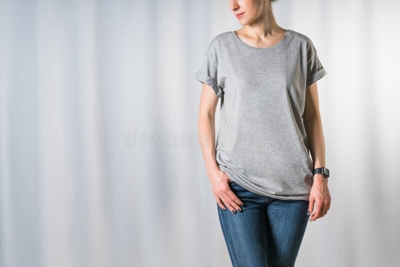 少妇正面图,穿戴在浅灰色的T恤杉和蓝色牛仔裤,站立在浅灰色的背景 免版税图库摄影