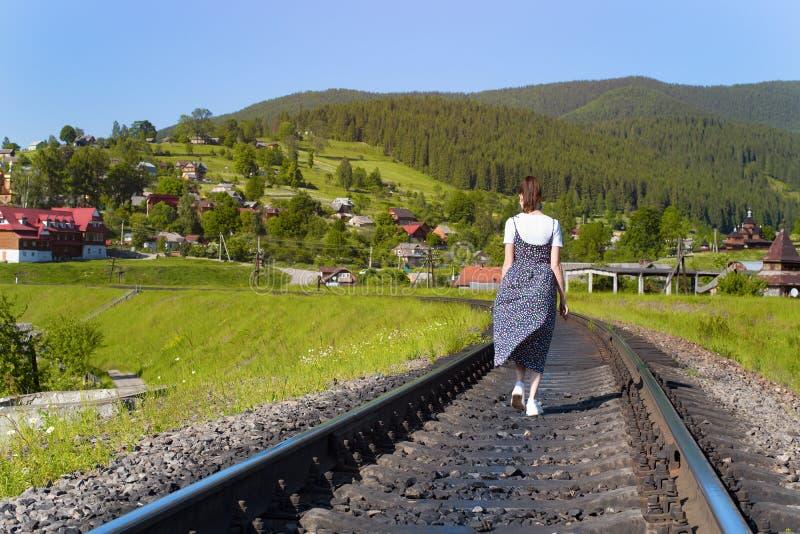 少妇沿铁路轨道走 绿色山 库存照片