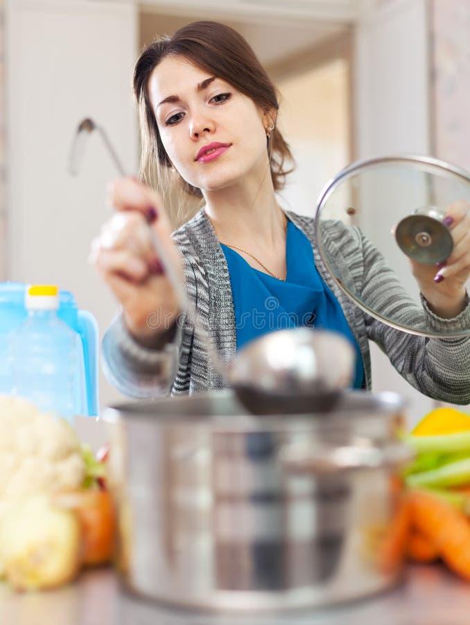 少妇测试与杓子的食物 库存图片