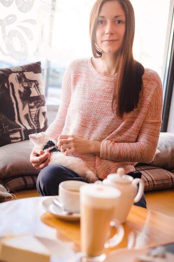 少妇消磨时间和她的在咖啡馆的宠物白鼬一起 免版税库存图片