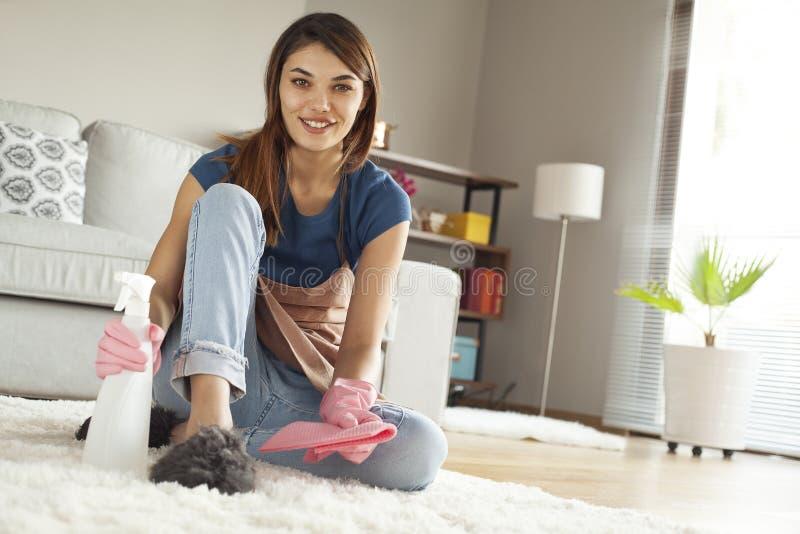 少妇清洁地毯在屋子里 免版税库存照片