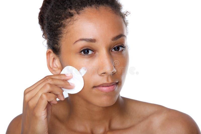 少妇清洁面孔与组成撤除海绵 免版税图库摄影
