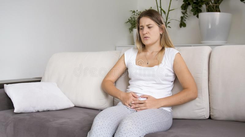 少妇照片有遭受在腹部的痛苦的期间的 免版税库存图片