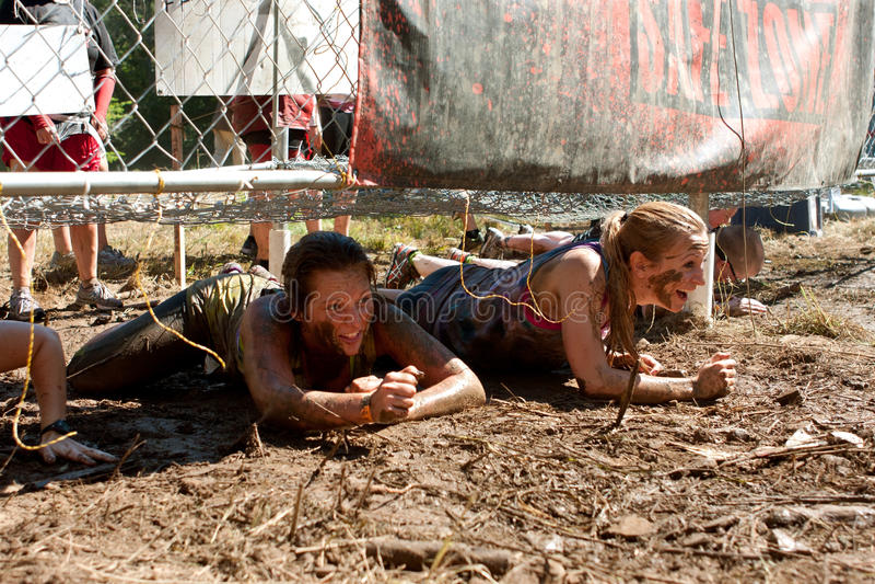 少妇爬行在5K越障竞赛的被使充电的篱芭下 免版税库存照片