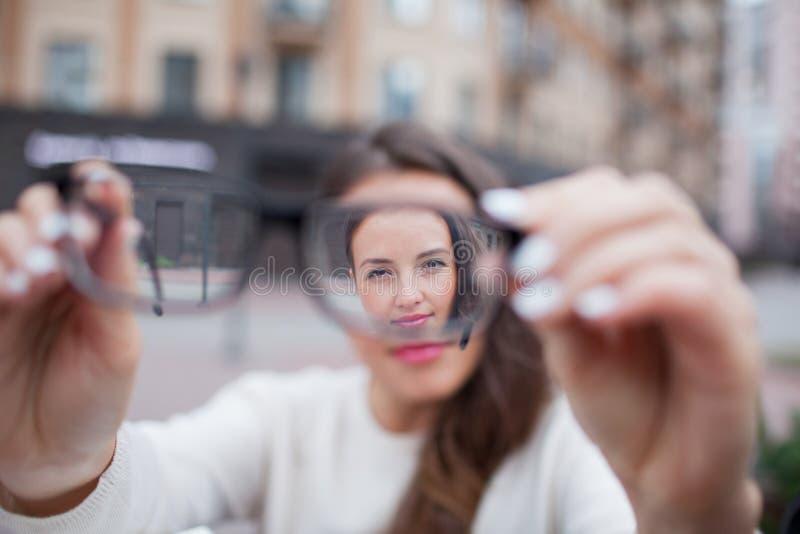 少妇特写镜头画象戴眼镜的 她有眼力问题和稍微斜眼看他的眼睛 美丽的女孩是 库存图片