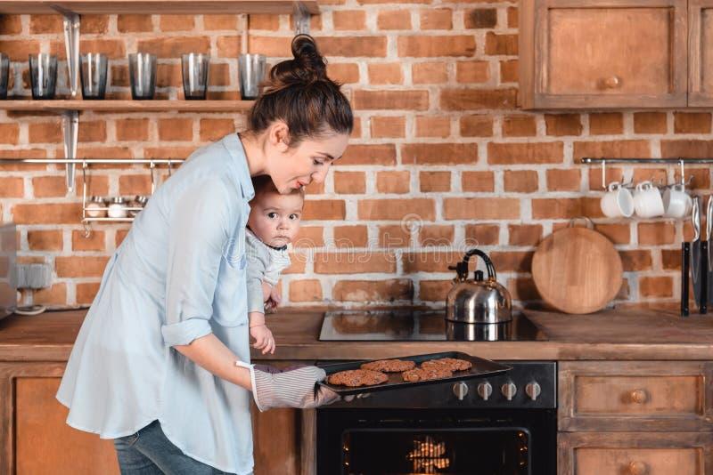 少妇用她的儿子烘烤曲奇饼在厨房里 库存图片