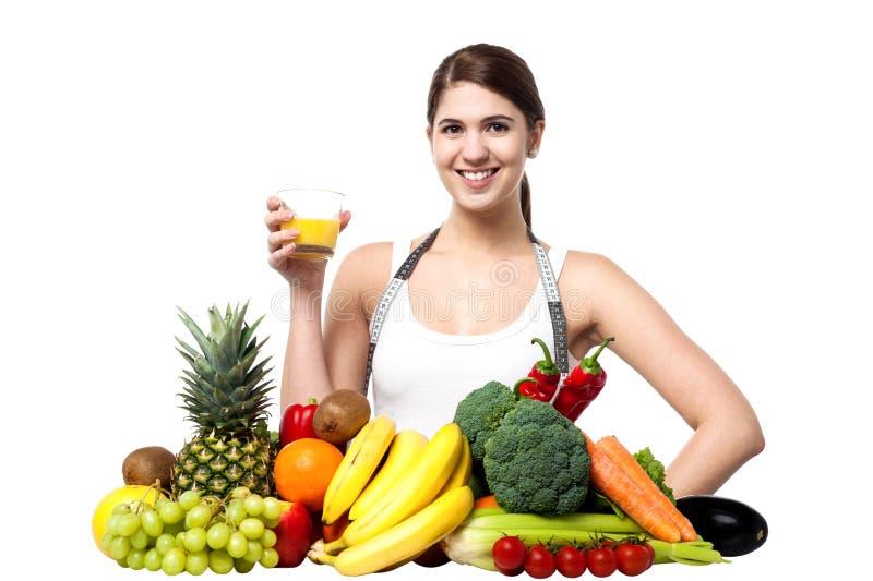 少妇用果子和杯汁液 免版税库存图片