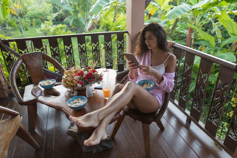 少妇用途细胞巧妙的电话,当在大阳台的早餐在热带庭院美好的女孩传讯网上吃时 免版税库存照片