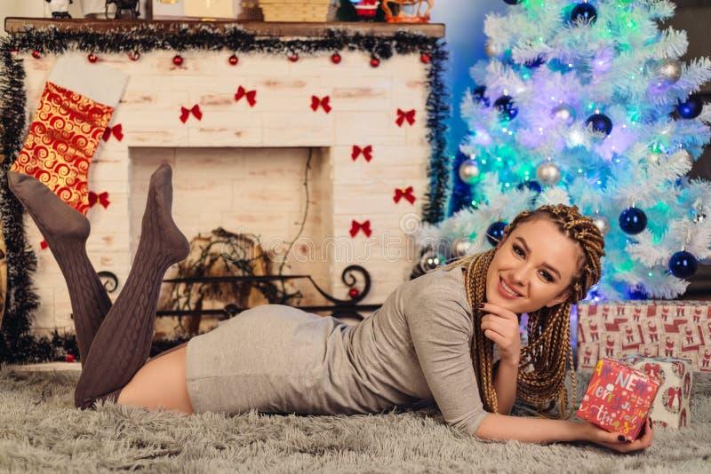 少妇由壁炉在她的手和一棵装饰的圣诞树上的说谎拿着一件礼物 图库摄影