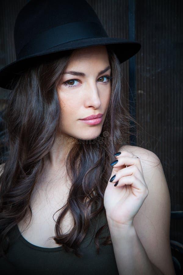 少妇画象与帽子夏日在城市 免版税库存照片