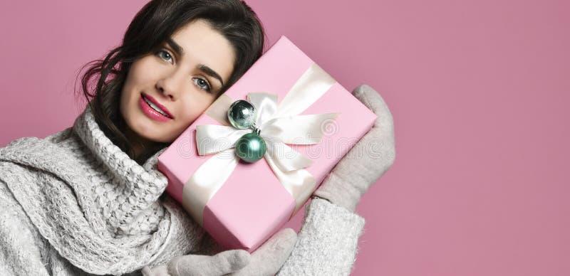 少妇画象举行礼物 桃红色背景的微笑的愉快的女孩 库存图片