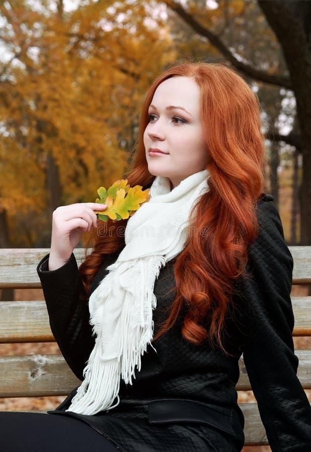 少妇画象在秋天公园,拿着叶子手中 库存图片