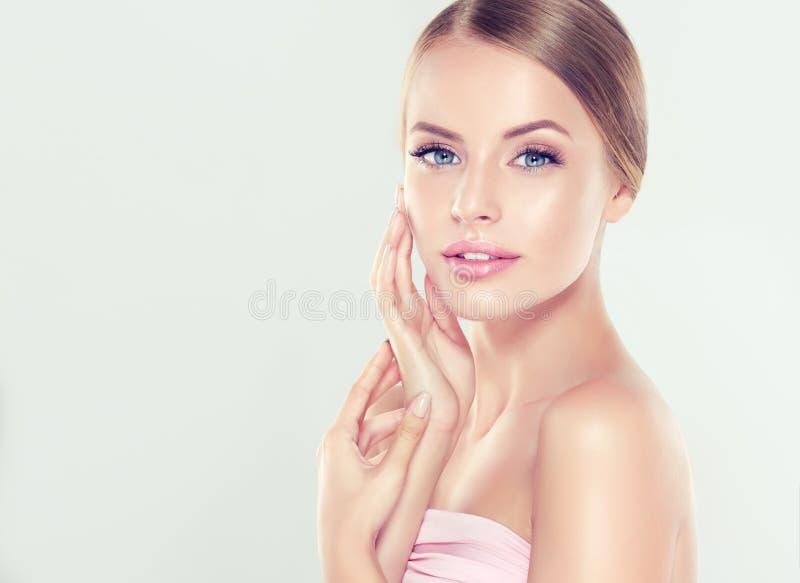 少妇画象有干净的新鲜的皮肤的和软,精美组成 妇女体贴接触对自己的面孔 免版税库存照片