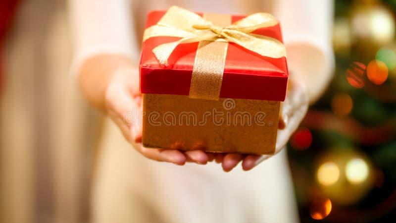少妇的特写镜头图象显示红色当前箱子的礼服的秘密审议 圣诞节礼物的概念 库存图片