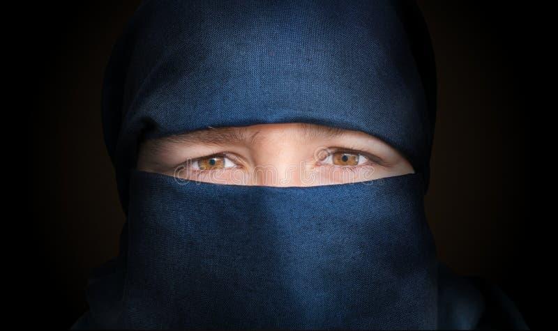 少妇的眼睛遮掩与蓝色niqab围巾 低调照片 免版税图库摄影