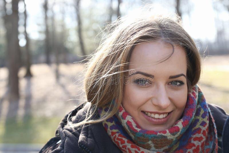 少妇的眼睛,当她微笑,她的头发在风吹 免版税库存图片