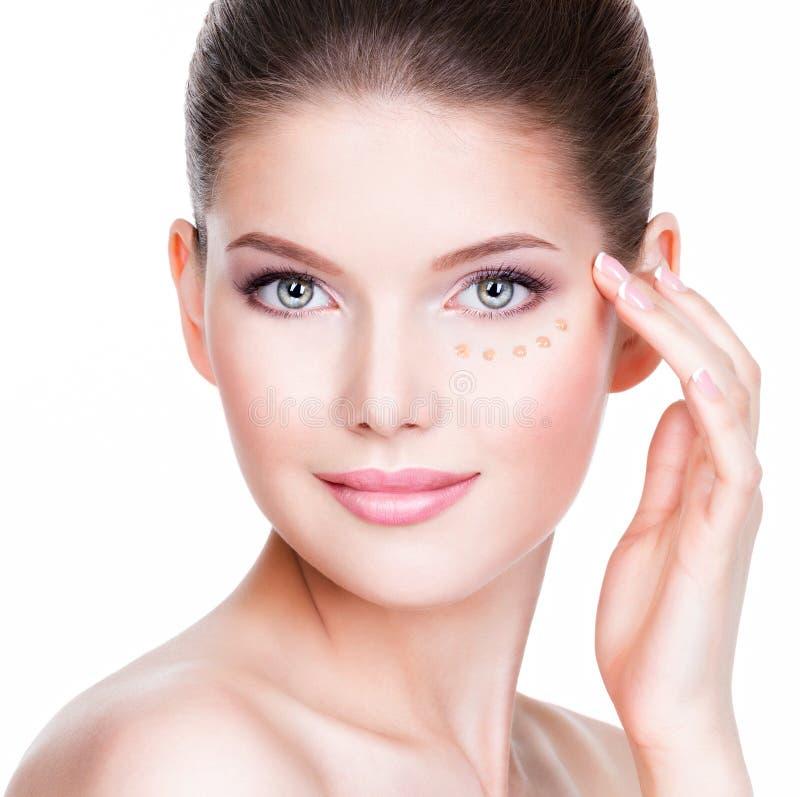 少妇的美丽的面孔有化妆基础的在皮肤 免版税库存照片