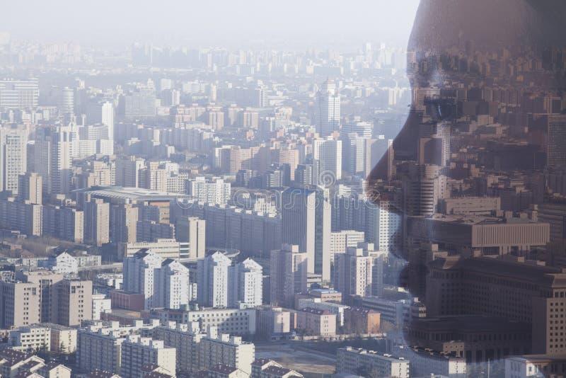 少妇的面孔两次曝光在都市风景,侧视图的 库存图片