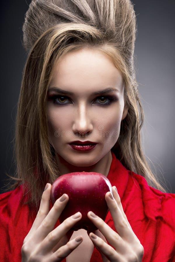 少妇的画象一条红色围巾的有拿着在灰色背景的手中红色苹果的先锋发型的 免版税图库摄影