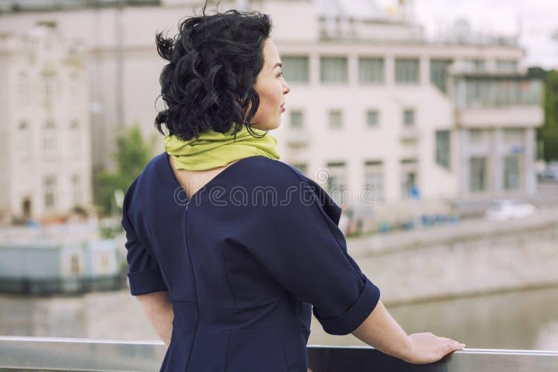 少妇看从桥梁的大城市 免版税图库摄影