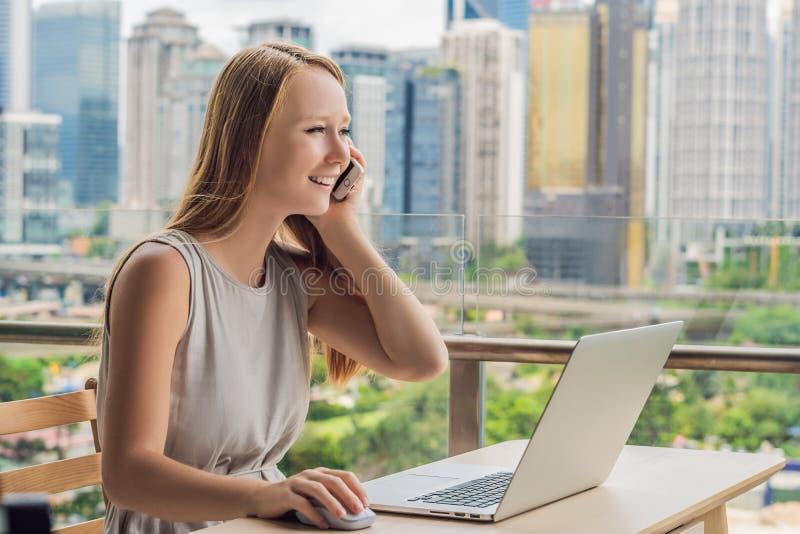 少妇研究在她的俯视摩天大楼的阳台的一台膝上型计算机 自由职业者,遥远的工作,从家的工作 免版税库存照片