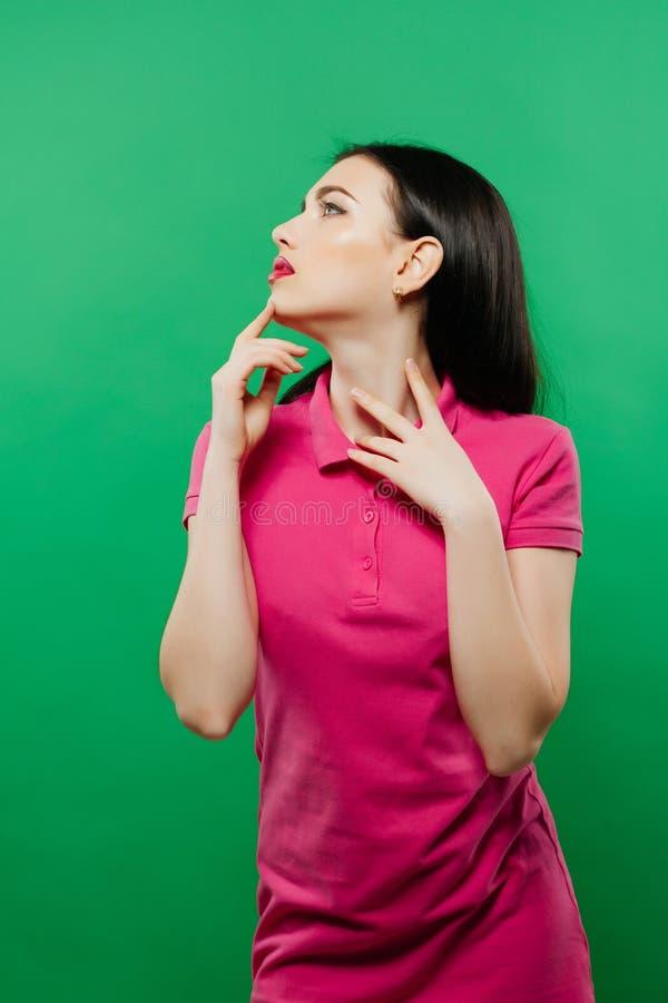 少妇秀丽画象有明亮的构成的在摆在绿色背景的桃红色衬衣 免版税库存图片