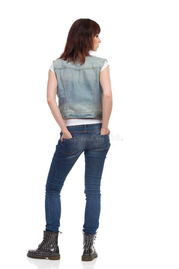 少妇站立,握在口袋的手并且看  查出的背面图白色 库存图片
