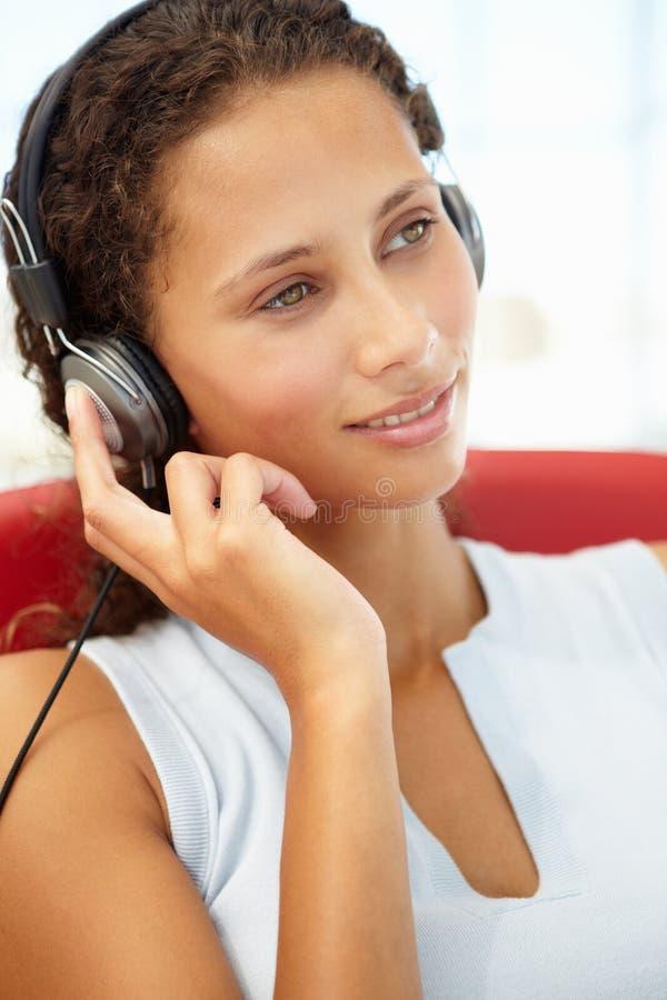 少妇纵向有耳机的 免版税库存图片