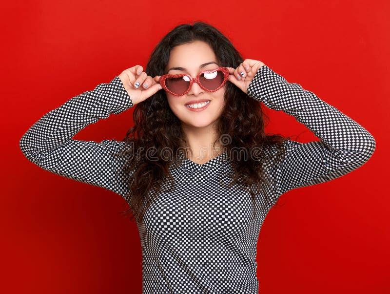 Download 少妇美丽的画象,摆在红色背景,长的卷发,太阳镜在心脏塑造,魅力概念 库存图片 - 图片 包括有 礼服, 拉丁语: 72366727