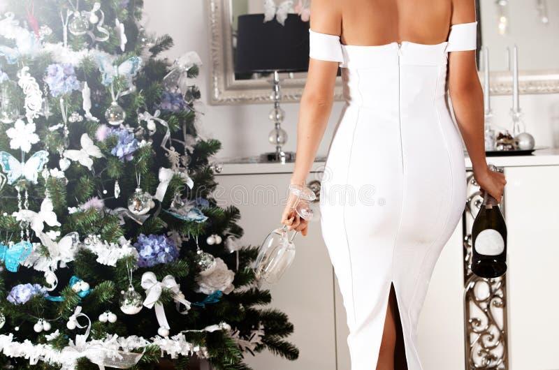 少妇美好的后面一件白色性感的礼服的有champag的 免版税库存照片
