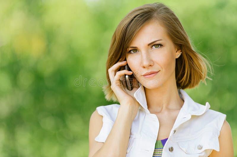 少妇联系在移动电话 免版税库存照片