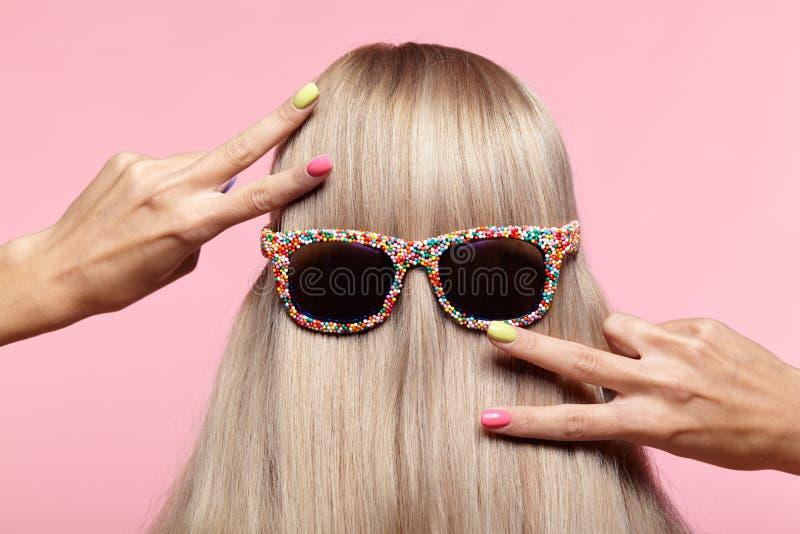 少妇背面图 有乐趣太阳镜的白肤金发的stright头发 库存照片
