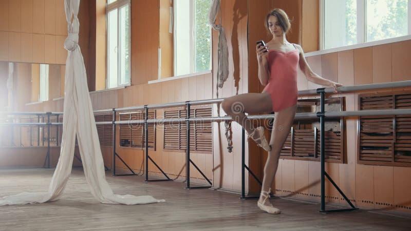 少妇舞蹈家用途智能手机在芭蕾屋子 免版税库存照片