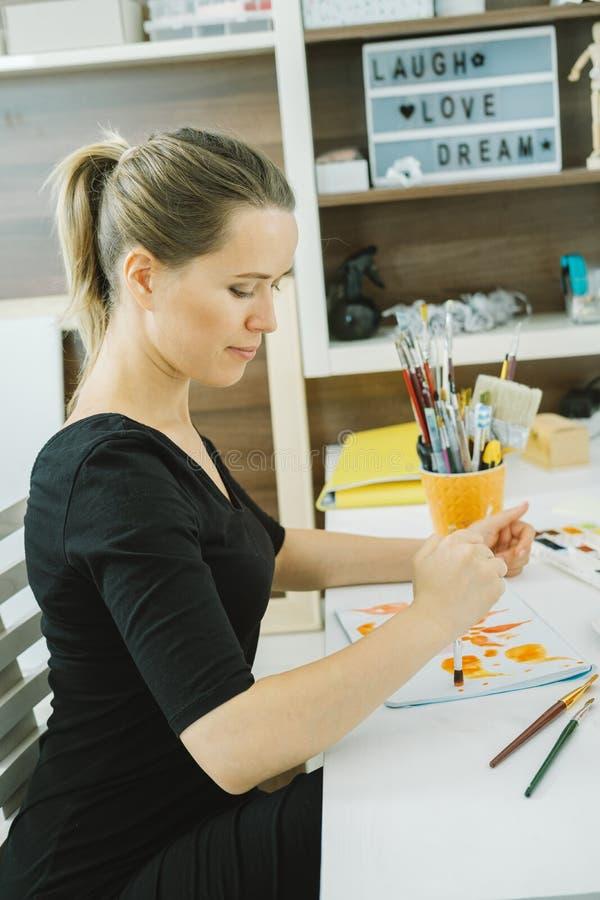 少妇艺术家在她的工作场所的图画剪影在演播室 免版税库存图片
