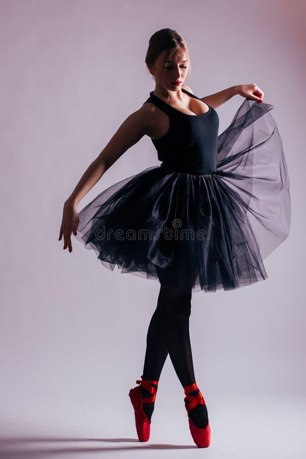 少妇芭蕾舞女演员与芭蕾舞短裙的跳芭蕾舞者跳舞在剪影 免版税库存图片