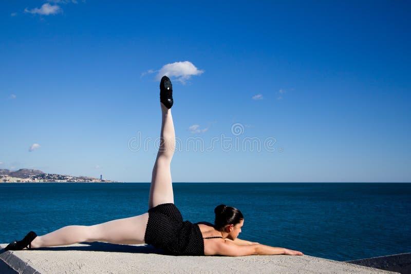 少妇行使她的在一个大石块的柔软在地中海前面 库存图片