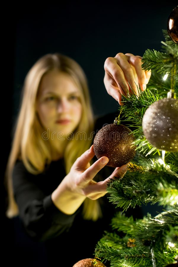 少妇装饰圣诞树 与装饰的云杉 库存图片