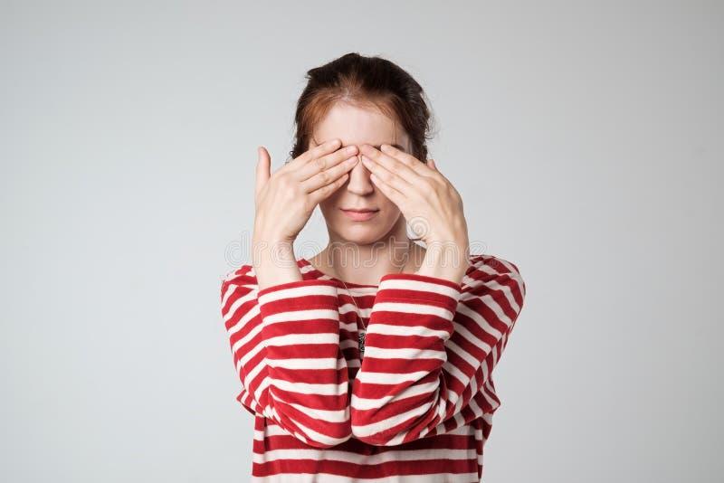 少妇覆盖物面孔用在灰色背景的手 免版税图库摄影
