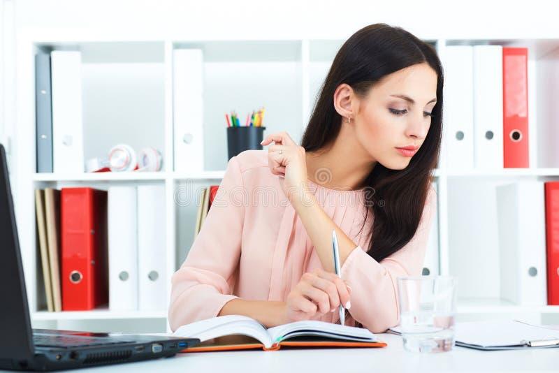 少妇读书裱糊坐她的工作场所 免版税图库摄影