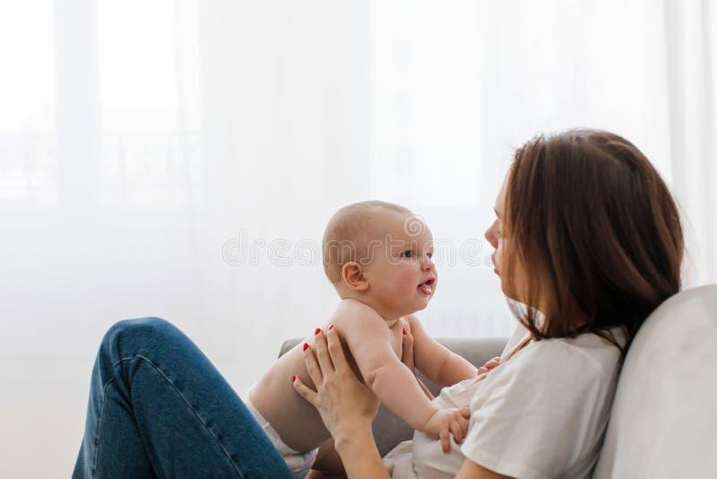 少妇谈话与沙发的婴孩 免版税库存图片