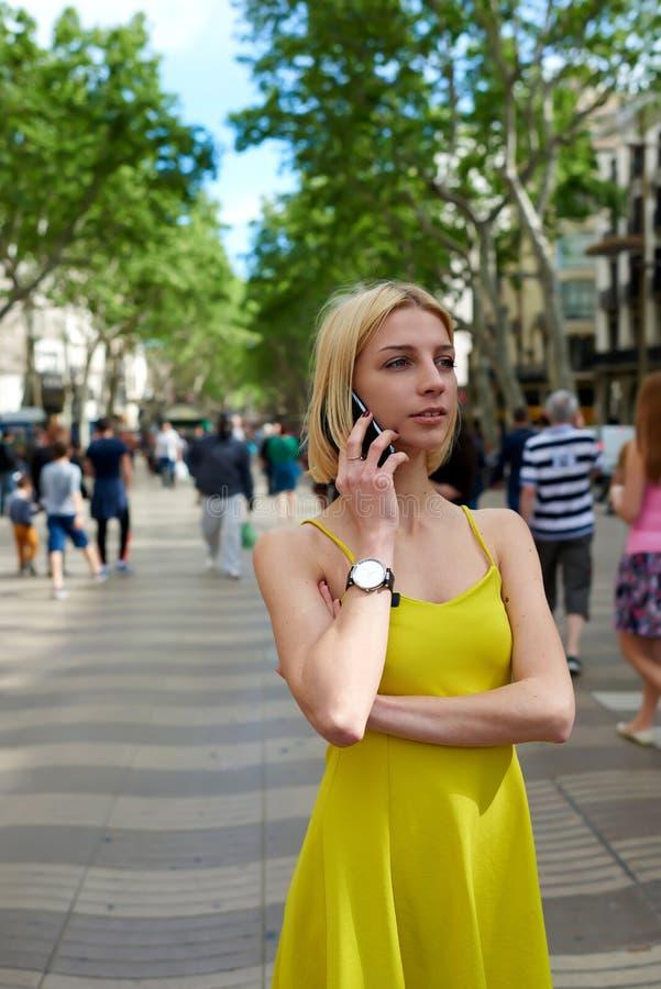 少妇谈话在她巧妙的电话,当站立在有人走的时城市街道 免版税库存照片